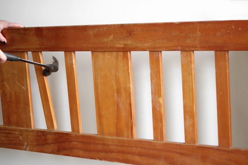 Gently remove slats from the headboard using a hammer.