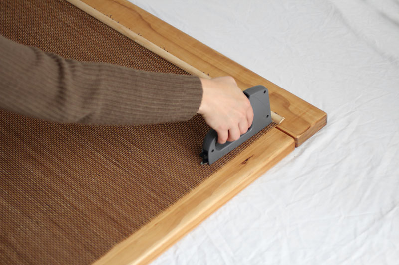 Staple the middle and all four corners of the blind to the headboard.